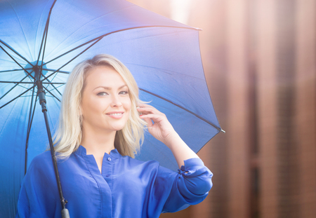 Beautiful young woman with blue umbrella in city center. Attractive woman in the street. Imagens