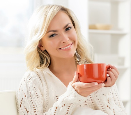 Beautiful smiling woman enjoying the smell of coffee in the morning. Stock Photo