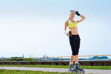 Patinaje en línea joven, hermoso, deportivo y en forma en patines en línea