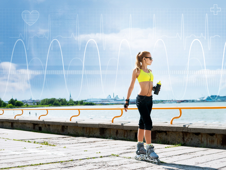 Young, beautiful, sporty and fit girl rollerblading on skates over imaginary digital background