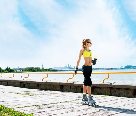Young, beautiful and fit girl over sky background. Sporty woman rollerblading on skates. Stock Photo