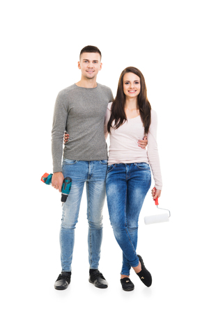 Young couple moving in a new home. Man and woman with tools and boxes.