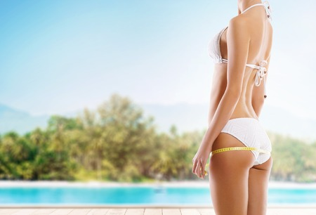 Sexy girl measuring perfect body. Summer beach background. Fat lose, sport and fitness concept. Standard-Bild
