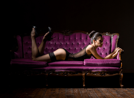 Sexy and beautiful woman in erotic lingerie and stockings posing on a magenta sofa in vintage interior. Stockfoto