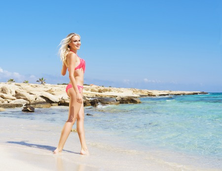 Beautiful, fit and sexy girl in pink swimsuit posing on a beach at summer. Sea and sky background. Stock Photo