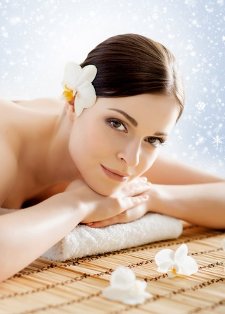 healer: Beautiful, young and healthy woman in winter spa salon. Massage treatment over Christmas background with snow. Traditional medicine and healing concept. Stock Photo