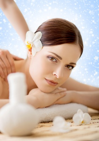 Beautiful, young and healthy woman in winter spa salon. Massage treatment over Christmas background with snow. Traditional medicine and healing concept. Stock Photo