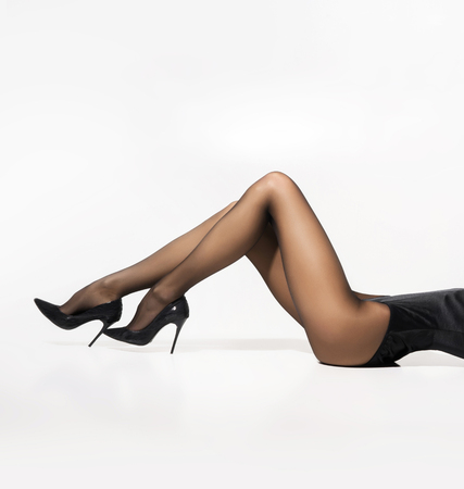 Beautiful legs in pantyhose over white background