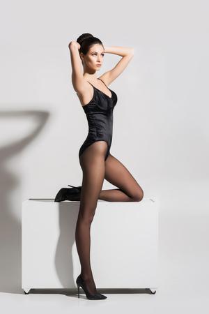 Mulher bonita, elegante que levanta em um cubo que veste o roupa interior e meias de fascínio.