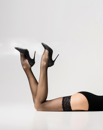 Beautiful legs in stockings over white background.