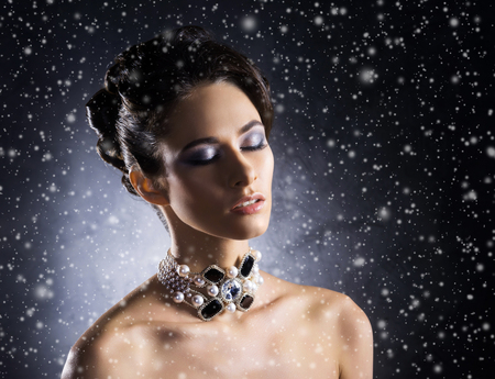 onyx: Young, beautiful and rich woman in jewels of platinum and stones over winter Christmas background