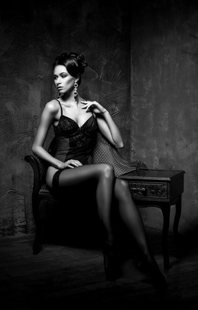 Woman in sexy lingerie and stockings posing in a vintage interior. Beautiful girl in erotic underwear. Black and white. Stock Photo