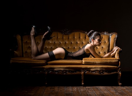 Sensual seductive young woman with sexy legs in hosiery posing in vintage interior.