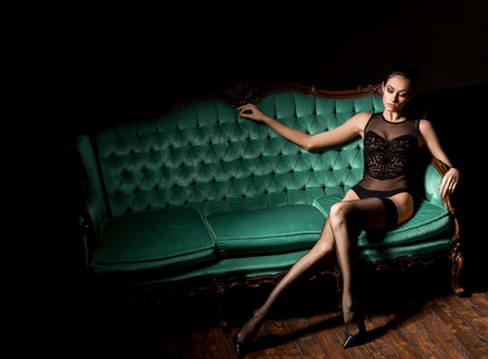 Sexy and beautiful woman in erotic lingerie and stockings posing on a green sofa in vintage interior.