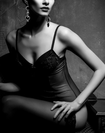 Woman in sexy lingerie and stockings posing in a vintage interior. Close-up of beautiful girl in erotic underwear. Black and white. Stock Photo