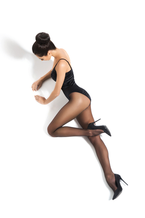 Mujer atractiva que desgasta la ropa interior atractiva, calcetería y los talones sobre el fondo aislado.