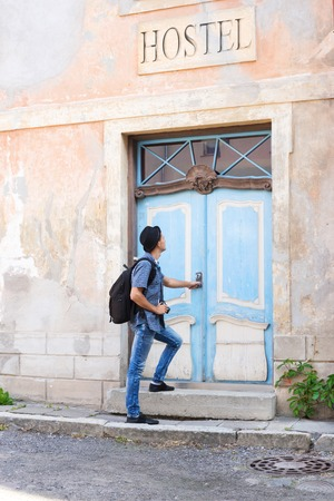 Handsome male tourist entering an old building (hostel, hotel or appartments). Traveling and couchsurfing concept.