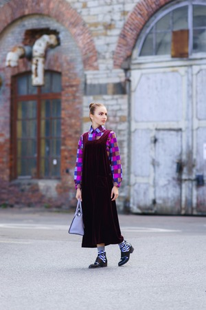Beautiful and pretty young girl; standing in front of abandoned factory. Fashion, beauty, retro, streetlook: concept.