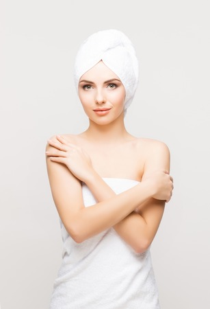 Young, beautiful and natural woman wrapped in towel isolated on white