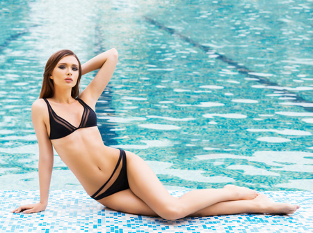 Young and sexy brunette woman in a swimsuit next to a swimming pool. Stock Photo