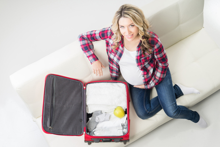 Young attractive pregnant woman packing childrens wear to go to maternity clinic. Stock Photo