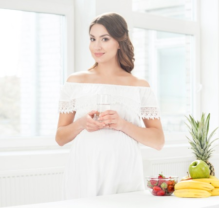 Pregnant woman with a glass of water. Healthy eating concept. Stock Photo