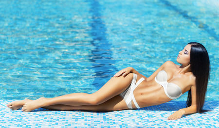 Beautiful and sporty lady in alluring swimwear getting a tan nearby swimming pool. Stock Photo