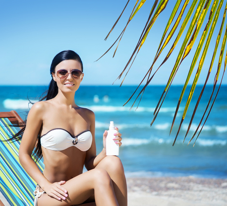 Gorgeous, young, sporty woman wearing sunglasses with a bottle of sunscreen lotion over background with sea and palm. Stock Photo