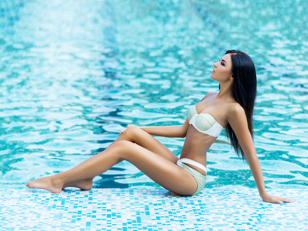 Gorgeous, sexy, slender lady in alluring swimwear tanning poolside.