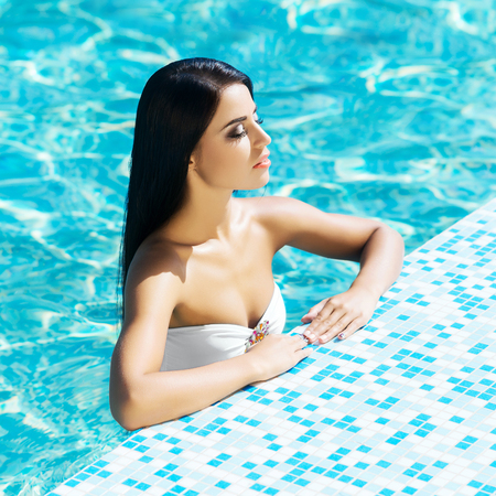 sexy latina: Portrait of beautiful, sensual woman relaxing in the swimming pool. Stock Photo