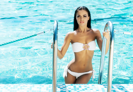 Young, gorgeous lady with thin and tanned body in sexy white bikini being in the swimming pool and holding rails.
