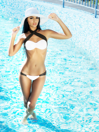 Absolutely gorgeous, young lady with perfect body wearing a hat and alluring bikini and standing in swimming pool.