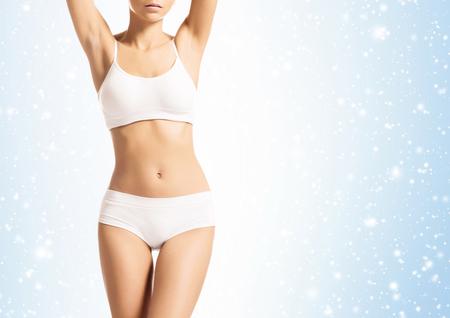 Chica joven, deportivo, en forma y hermosa en ropa interior deportiva sobre fondo de Navidad con nieve. Foto de archivo