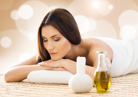 Young and beautiful girl relaxing in spa salon. Massage therapy, healing medicine and health care concept.