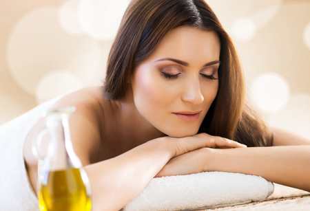 Beautiful, young and healthy woman in spa salon. Massage treatment, traditional medicine and healing concept.