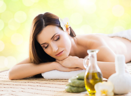 Young and beautiful girl relaxing in spa salon. Massage therapy over seasonal summer or spring background. Healing medicine and health care concept.