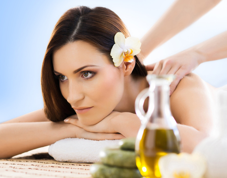 healer: Beautiful, young and healthy woman in spa salon. Massage treatment, traditional medicine and healing concept. Blue background.