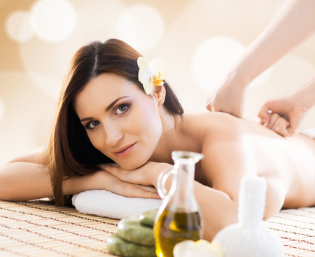 healer: Young and beautiful girl relaxing in spa salon. Massage therapy, healing medicine and health care concept.