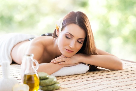 healer: Beautiful, young and healthy woman in spa salon. Massage treatment over green summer or spring background. Traditional medicine and healing concept. Stock Photo