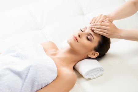 healer: Beautiful woman laying on a mat in massage salon.