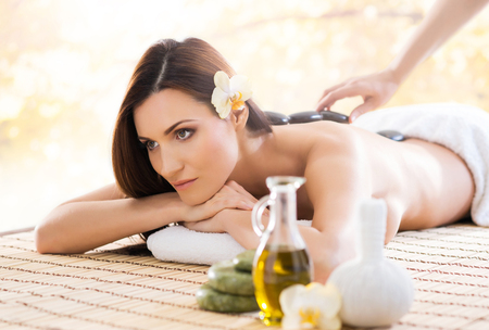 healer: Beautiful woman laying on a mat having a smell of aroma in spa salon.