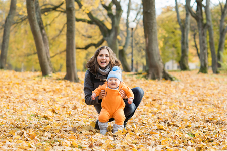 Mother teaching her toddler son to walk in the park. Autumn nature background. Love and family concept.
