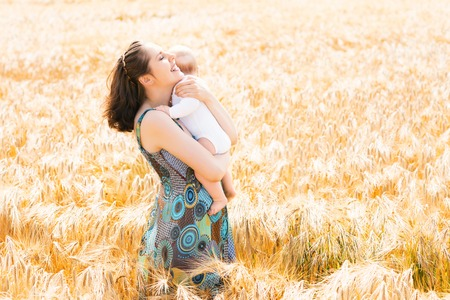 Young and beautiful woman playing with her infant baby in a meadow of wheat. Summer concept. Фото со стока