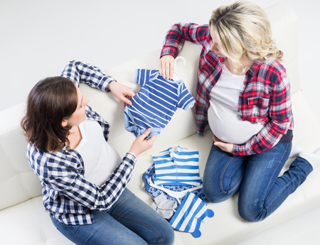 Two expectant mothers checking out childrens wear.