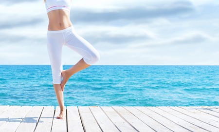 Attractive girl in white sporty clothes doing yoga on a wooden pier. Yoga, sport, leisure, recreation and freedom concept. Stockfoto