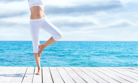 Attraktives Mädchen in der weißen sportlichen Kleidung, die Yoga auf einem hölzernen Pier tut. Yoga, Sport, Freizeit, Erholung und Freiheitskonzept. Standard-Bild - 90927475