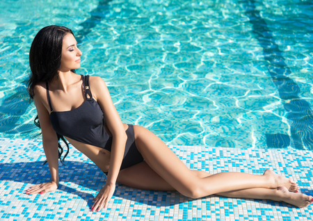 Beautiful and sexy woman in a swimwear relaxing near swimming pool. Traveling and vacation concept.