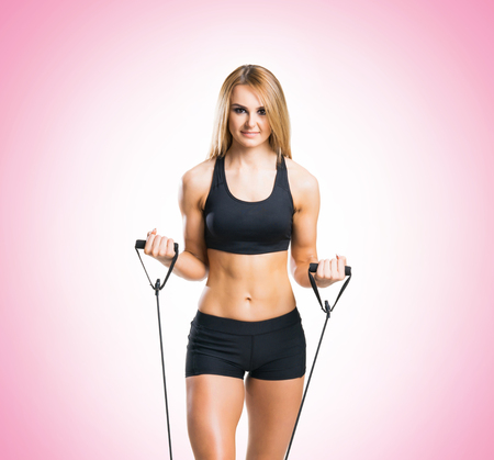Fit, healthy and sporty girl in sportswear doing expander exercise pink background.
