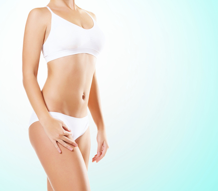 Fit and sporty girl in white underwear. Beautiful and healthy woman posing over green background. Sport, fitness, diet, weight loss and healthcare concept.