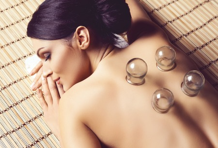 Healthy and beautiful woman getting massage treatment in spa salon. Stock Photo